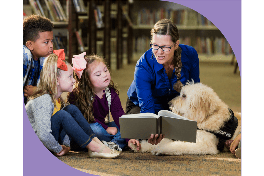 librarian reading to students with a therapy dog