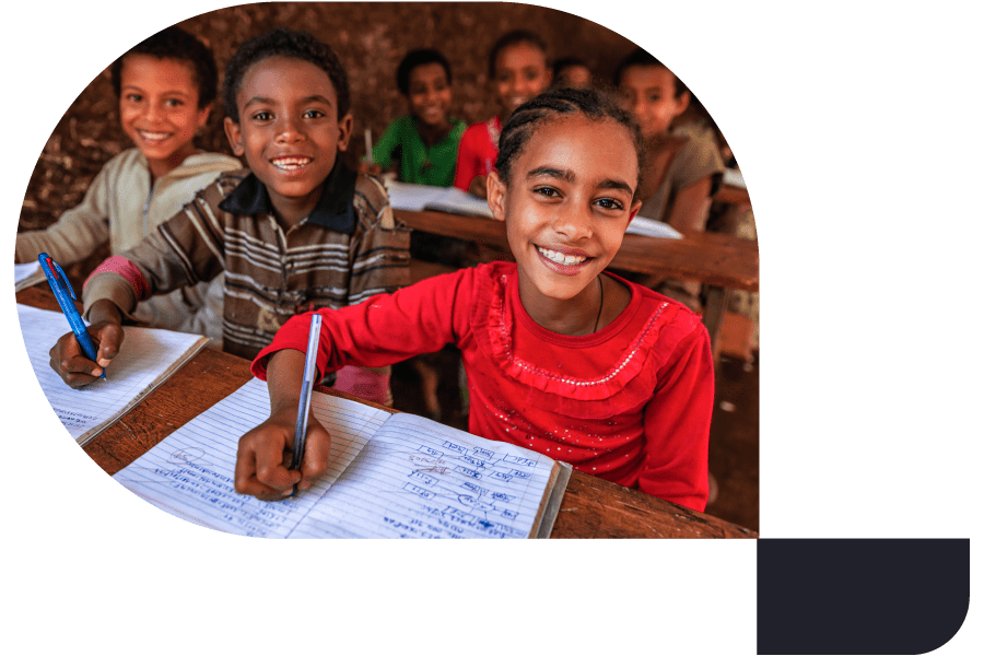 happy children taking notes in a classroom