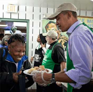 President Obama handing out food while volunteering at SOME