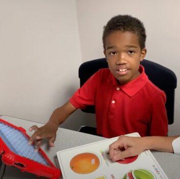teacher guiding child on a tablet