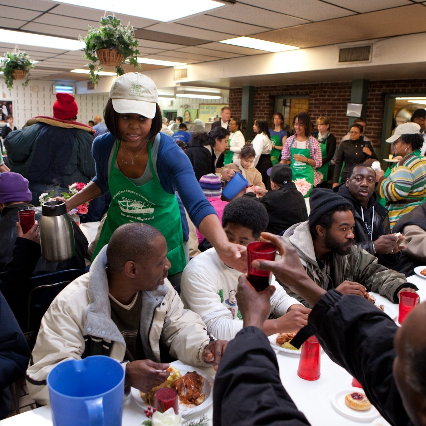 Michelle Obama handing out food while volunteering at SOME