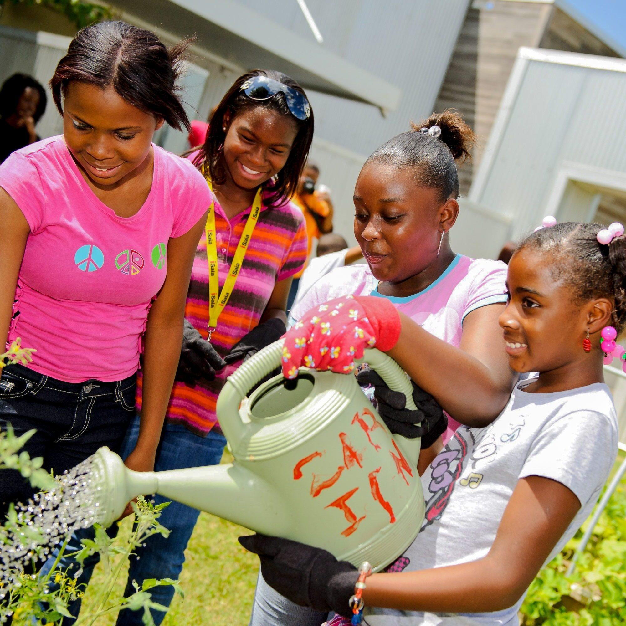group of girls watering plants