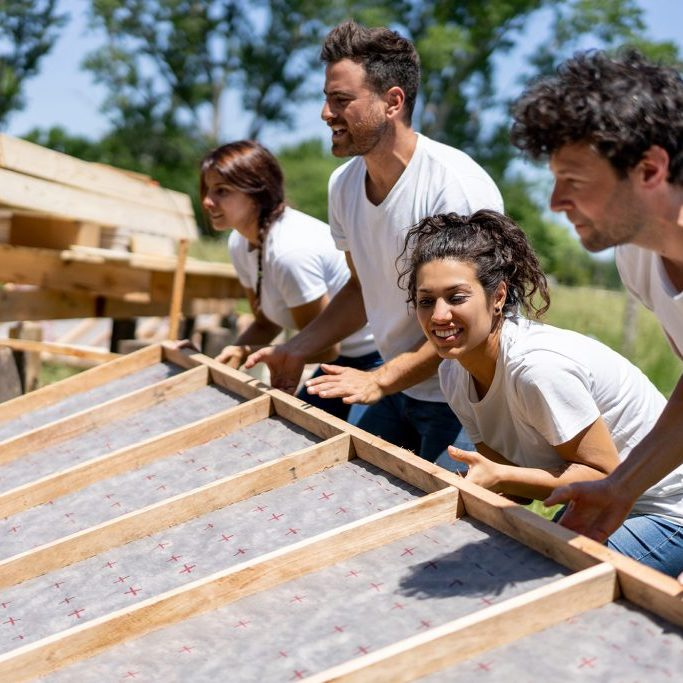 volunteers help pull up a wall for a house under construction