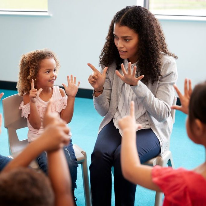 teacher guiding young children to count numbers with their fingers