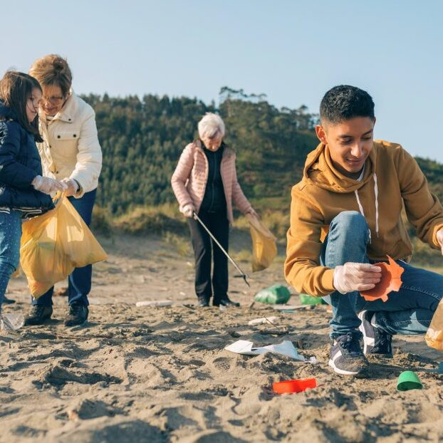 group of people picking up litter at a beach