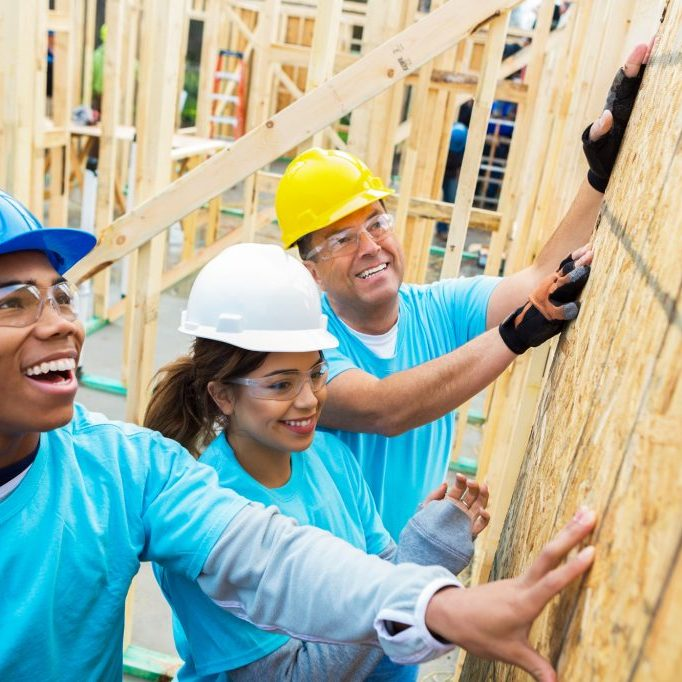 volunteers help push up a wall for a house under construction