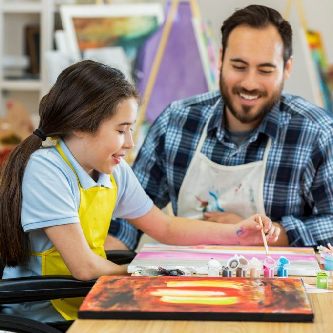 art teacher helping young child with a painting